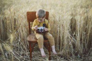 Das Kind sitzt auf dem Stuhl.